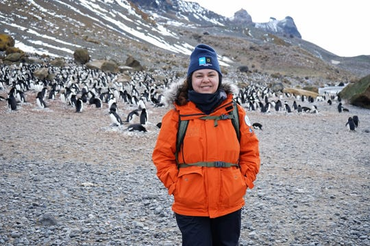 Santa Teresa High School science teacher Monica Nuñez, during her 2017-18 trip to Antarctica, flanked by penguins.