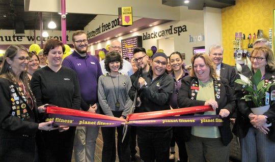 Planet Fitness Manager Nicole Lesansee , center, cuts the ribbons marking Planet Fitness' grand opening Wednesday.