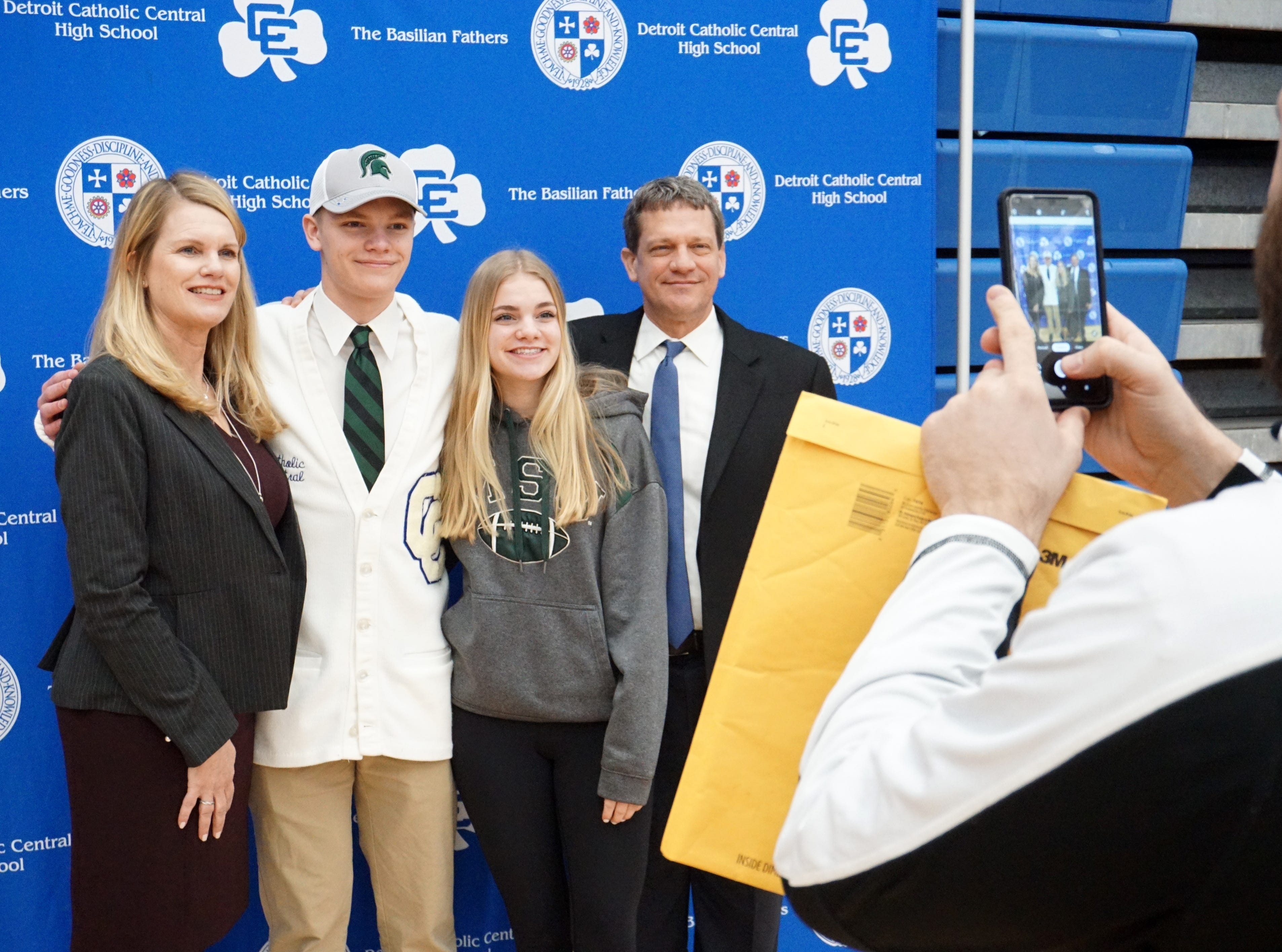 Catholic Central Shamrock Andrew Nicholsen, who will be attending MSU on an athletics scholarship, poses with his mom Gerilyn, sister Taylor, and father Hans at the school's Feb. 7 Signing Day ceremony. Director of admissions Jake Marmul, snaps a cell phone photo at right.