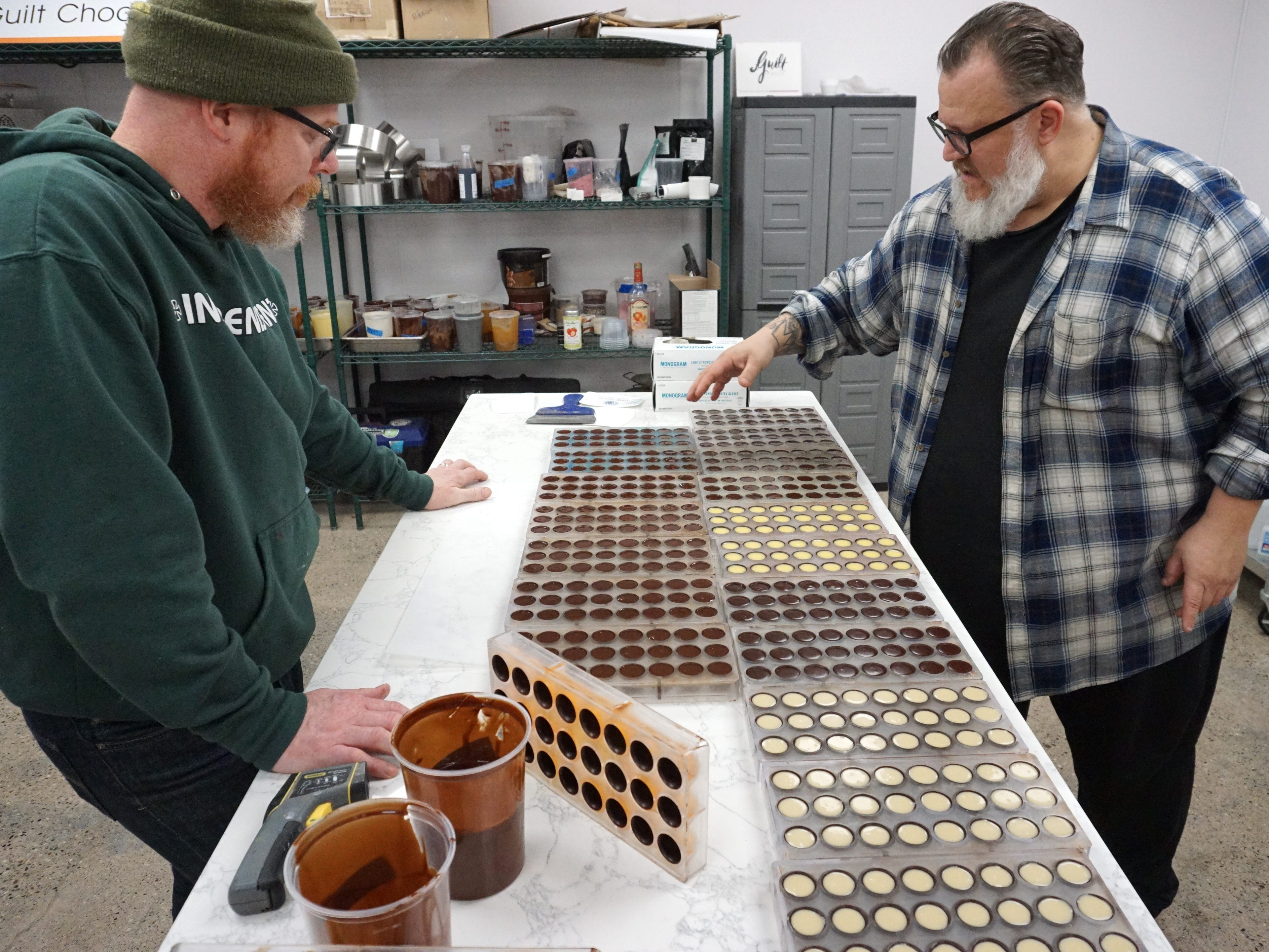 Guilt Chocolates' Scott Breazeale, left, and Joe Nader check out some of their production at their Seven Mile shop.