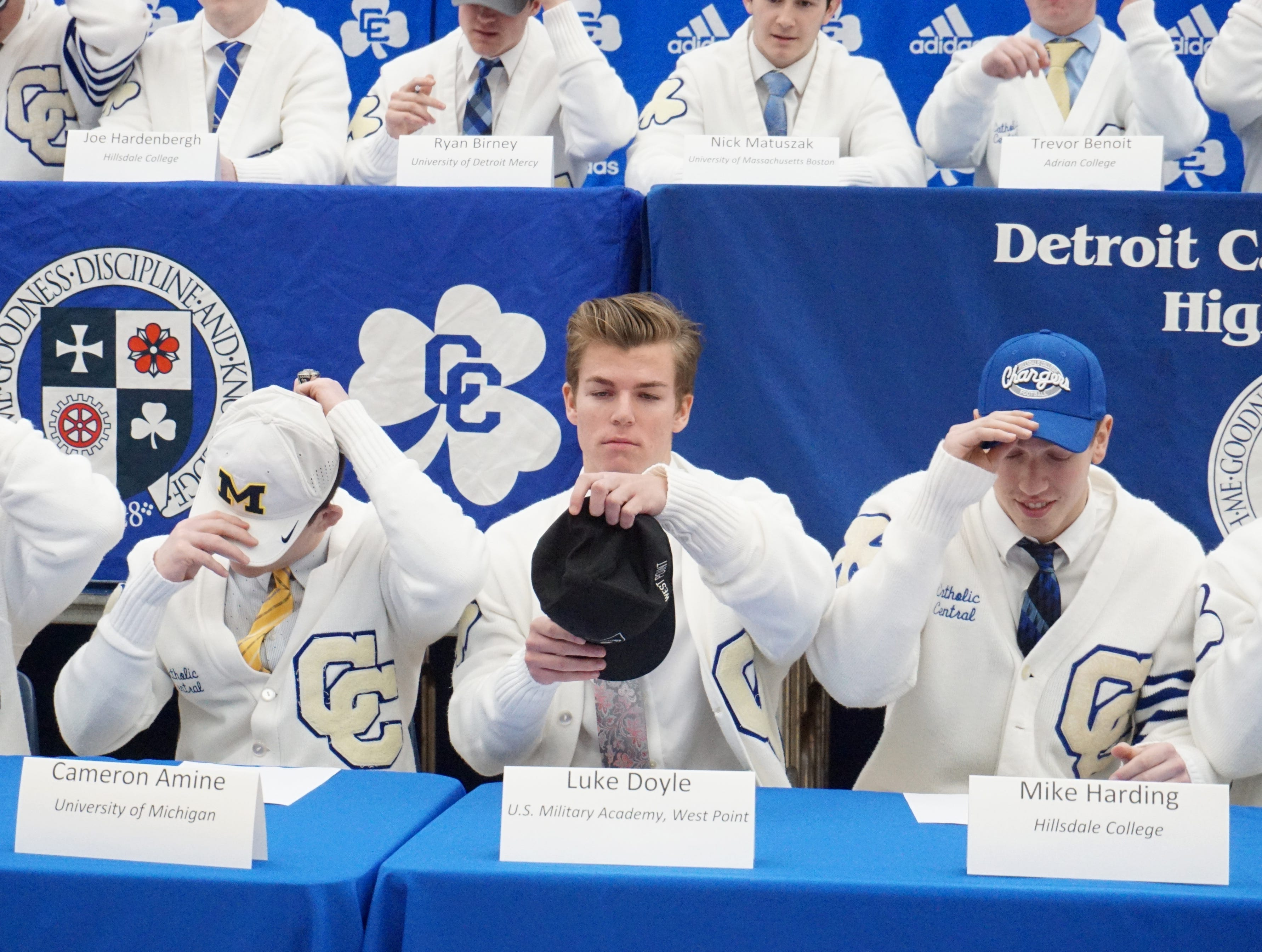 Catholic Central Shamrocks, including - from left: Cameron Amine, Luke Doyle and Mike Harding, don their schools-to-be caps at CC's Feb. 7 Signing Day ceremony.