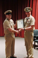NAS Whiting Field Commanding Officer Capt. Paul Bowdich presents a retirement certificate to Command Master Chief Lee Stephens at a ceremony celebrating Stephens' 30 year naval career.