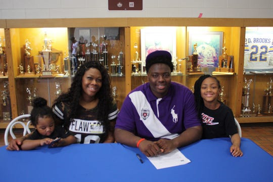 Booker T. Washington offensive lineman Timothy Robinson (center) poses with his family after signing a scholarship to play football at Miles College on Thursday, Feb. 7, 2019.