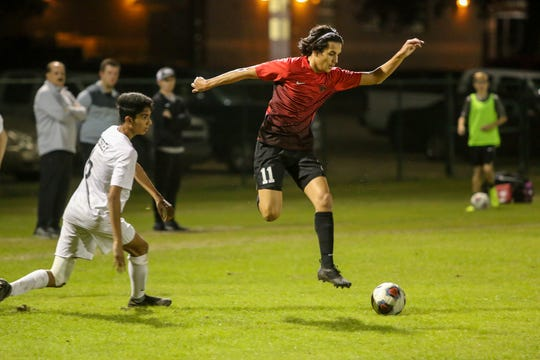 West Florida's Ron David Holland (11) jumps to avoid a tackle attempt by Mosley's Shaheer Zabih (6) in the Region 1-3A quarterfinal game at Ashton Brosnaham Park on Wednesday, February 6, 2019. Mosley beat West Florida 2-1 and advances to the next round.