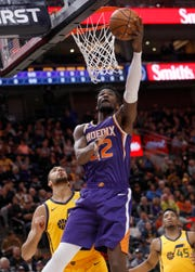 Phoenix Suns' Deandre Ayton (22) attempts a layup as Utah Jazz center Rudy Gobert, left, defends in the first half of an NBA basketball game on Wednesday, Feb. 6, 2019, in Salt Lake City.