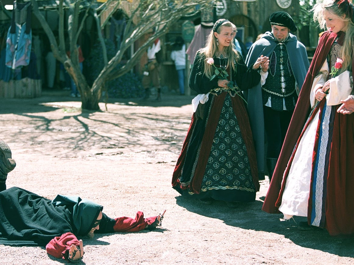 "Renaissance Festival performer Dave Weise, known as ""Farquahr the Highway Man,"" bows to the English nobility in 2001."