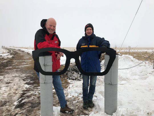 Arizona Republic reporter Jeff Metcalfe (right) poses for a picture with a statue of Buddy Holly's iconic glasses at the site of the singer's fatal 1959 plane crash.