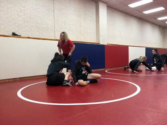 Moon valley wrestling, coach Peggy Sue Armstrong works with wrestlers during practice.