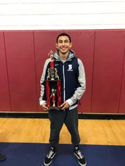 Mark Sanchez of Tempe wrestling team stand holding his trophy.