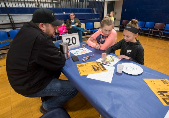 Bill Tarte sits with his daughters Kailey, 14, center, and Alexis, 11 after eating breakfast at the annual Super Dads and Donuts Thursday, Feb. 7, 2019 at Memphis Elementary School.