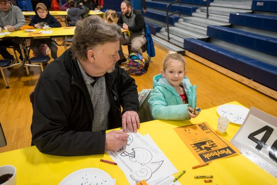Charles Deeren, left, colors while his granddaughter Lillie, 6, eats a donut at the annual Super Dads and Donuts Thursday, Feb. 7, 2019 at Memphis Elementary School.