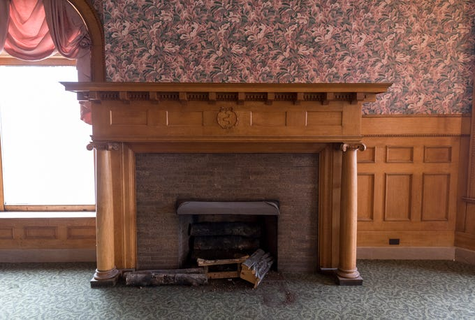 The fireplace in the hotel's lobby. Developers plan to remove the carpet and update the wallpaper in the lobby during renovations.