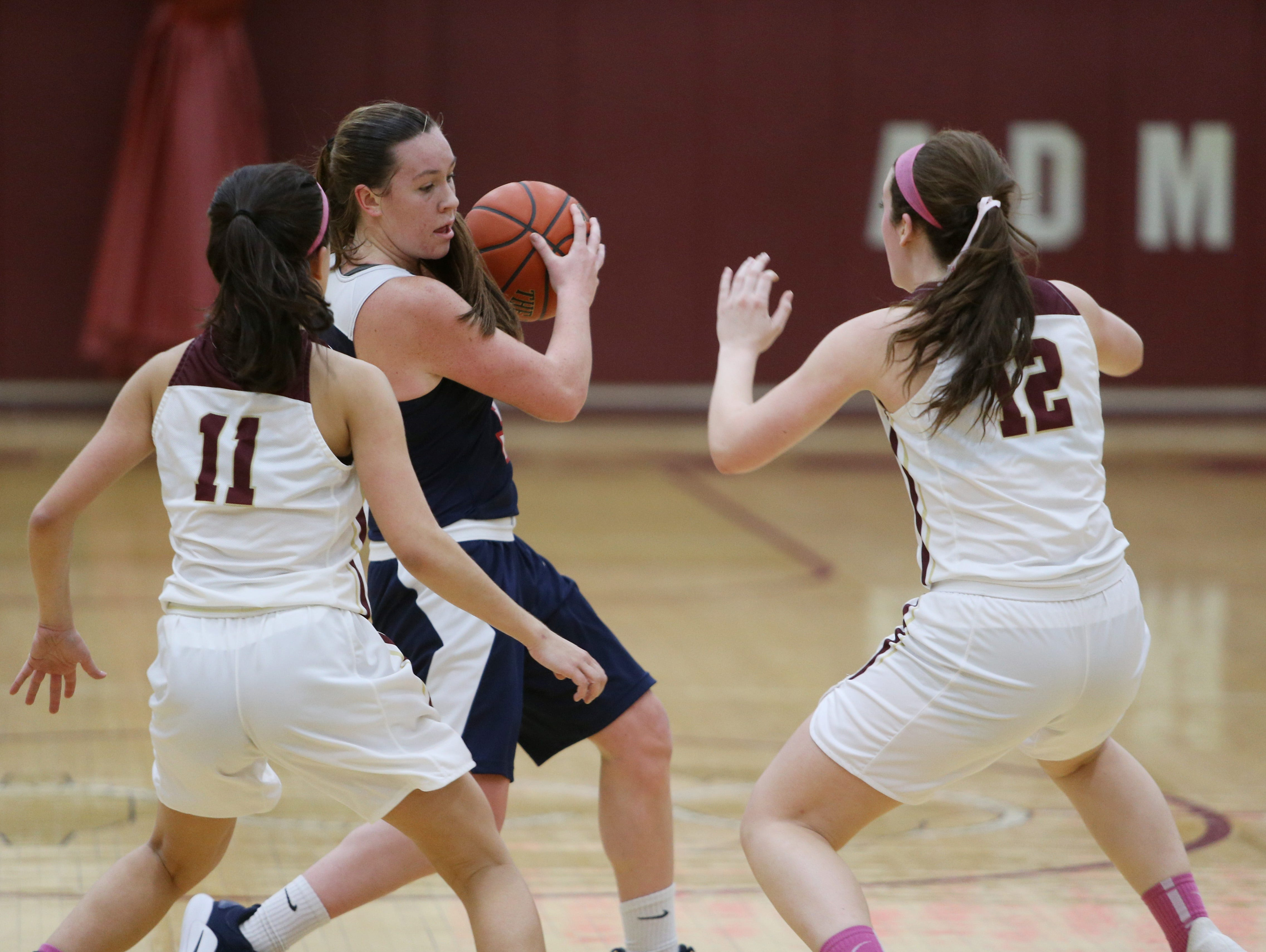 Ketcham's Katie Wall fends off Arlington's, from left, Camille Loussedes and Molly Stephens during Wednesday's game in Freedom Plains on February 6, 2019.