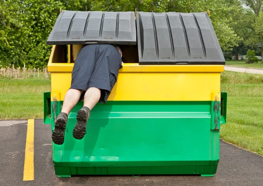 A man jumps into a dumpster.