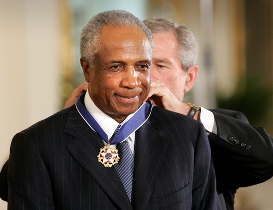 FILE - In this Nov. 9, 2005, file photo, President Bush awards baseball legend Frank Robinson the Presidential Medal of Freedom Award in the East Room of the White House in Washington. Hall of Famer Frank Robinson, the first black manager in Major League Baseball and the only player to win the MVP award in both leagues, has died. He was 83. Robinson had been in hospice care at his home in Bel Air. MLB confirmed his death Thursday, Feb. 7, 2019.(AP Photo/Lawrence Jackson, File)