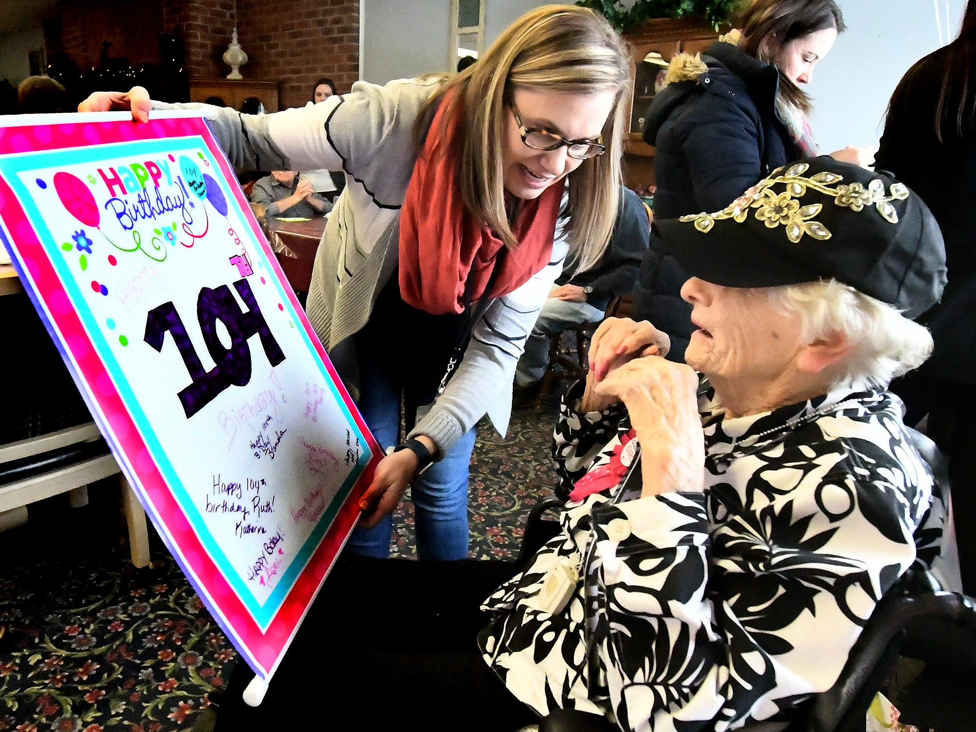 Memorial White Rose Home Health and Hospice social worker Katherine Walker shows Ruth Kohler a banner her staff made for Ruth's 104th birthday celebration at Senior Commons at Powder Mill where she is a resident Friday, Feb. 1, 2019. According to Senior Commons staff, Ruth is the oldest resident to have lived there. Bill Kalina photo