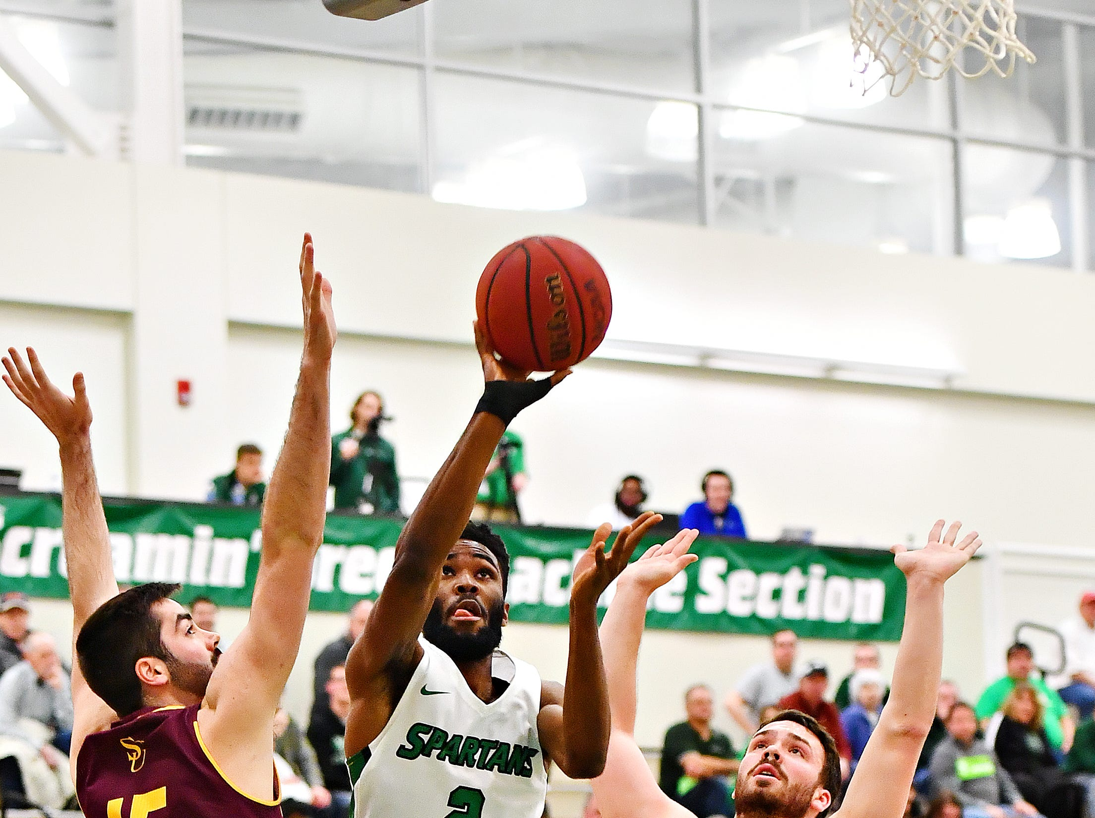 York College's Jason Bady, center, takes the ball to the basket while Salisbury's James Foley, left, and Chase Kumor defend during men's basketball action at Grumbacher Sport and Fitness Center at York College of Pennsylvania in Spring Garden Township, Wednesday, Feb. 6, 2019. Dawn J. Sagert photo