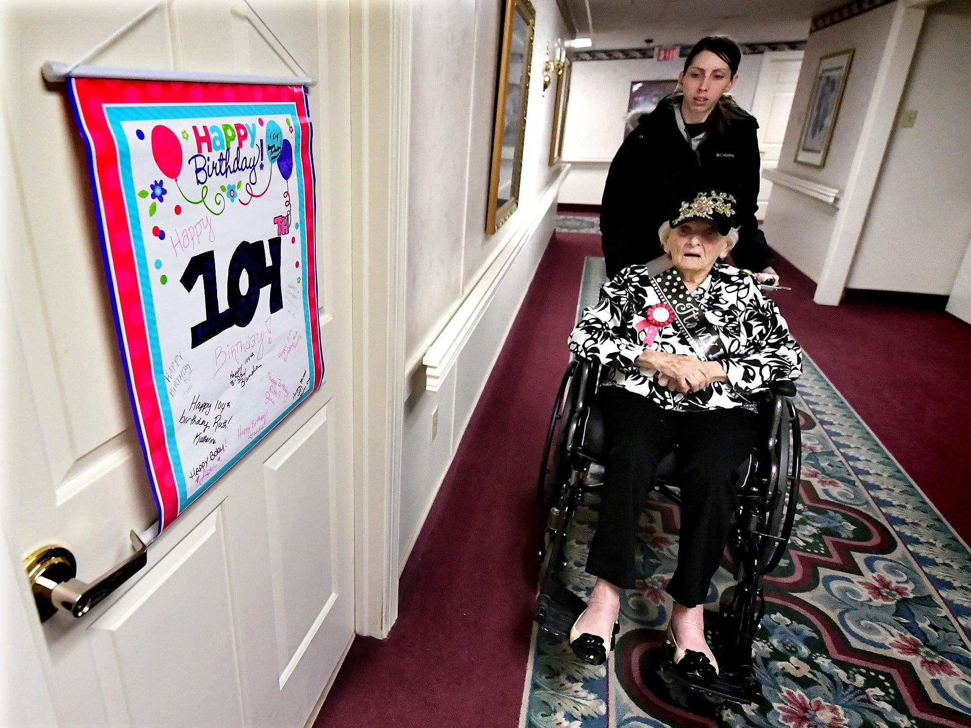 Memorial White Rose Home Health and Hospice aide Brittany Hare takes Ruth Kohler back to her room after Ruth's 104th birthday celebration at Senior Commons at Powder Mill where Ruth is a resident Friday, Feb. 1, 2019. According to Senior Commons staff, she is the oldest resident to have lived there. Bill Kalina photo