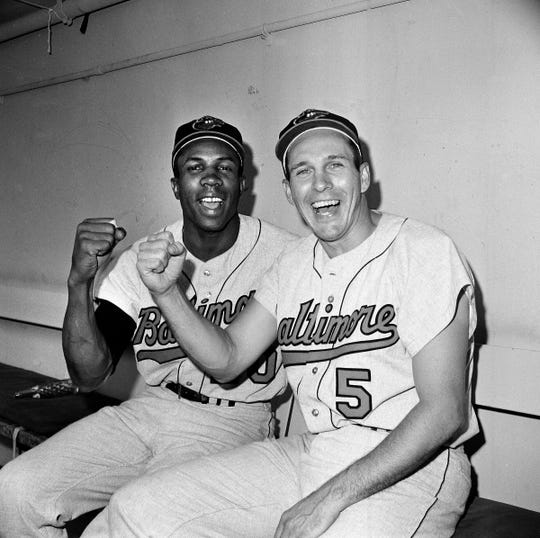 FILE - In this Oct. 5, 1966, file photo, Baltimore Orioles teammates Frank Robinson, left, and Brooks Robinson pose after leading the Baltimore Orioles to a 5-2 win in the opening game of the World Series against the Los Angeles Dodgers, in Los Angeles. Hall of Famer Frank Robinson, the first black manager in Major League Baseball and the only player to win the MVP award in both leagues, has died. He was 83. Robinson had been in hospice care at his home in Bel Air. MLB confirmed his death Thursday, Feb. 7, 2019.(AP Photo/File)