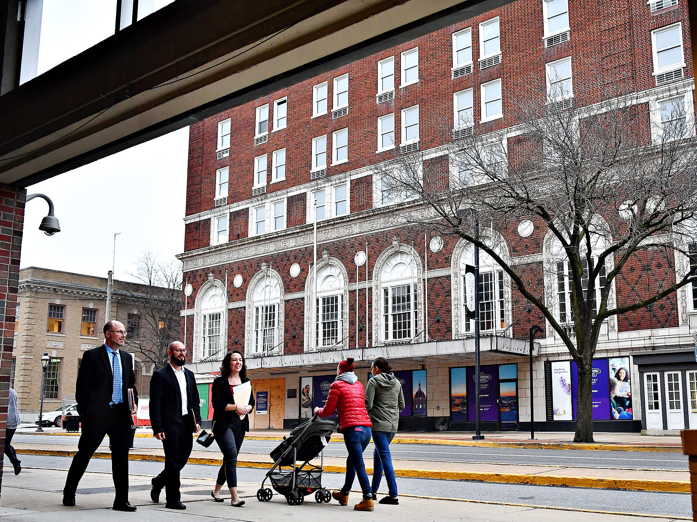 From left, Mark Duffie, of Fairview Township, Alison Irizarry, and Nick Irizarry, both of Dover Township walk across the street from the Yorktowne Hotel in York City, Thursday, Feb. 7, 2019. Yorktowne Hotel renovation costs have nearly doubled since original 2016 announcement. Dawn J. Sagert photo