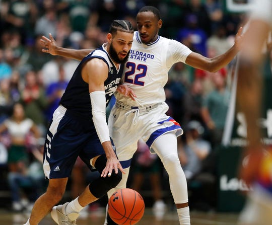 Nevada forward Cody Martin, left, is defended by Colorado State guard J.D. Paige during the second half Wednesday in Fort Collins, Colo. Nevada won 98-82.