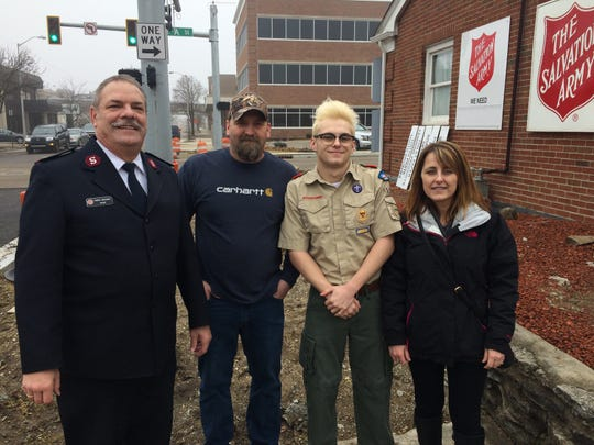 Boy Scout Brandon Mooney poses with Salvation Army Major Tom Brockway and his parents, Jason Mooney and Blerina Mooney, after hanging his Eagle Scout project on the side of the Salvation Army building at 707 S. A St.