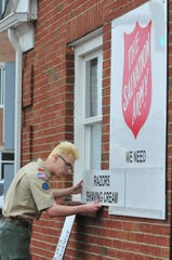 Brandon Mooney slides a placard asking for razors and shaving cream into place on his Eagle Project sign for the Salvation Army.