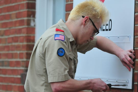 Brandon Mooney hangs his Eagle Scout project on the west wall of the Salvation Army building at 707 S. A St.