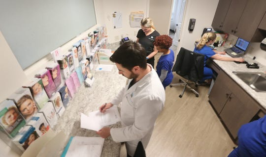 Dr. Joshua Weitz, CEO of Dermatology Associates of Rochester, and staff check over reports and information before meeting with patients.
