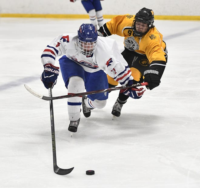 Fairport's Caleb Kaiser, left, shields the puck from McQuaid's Zack Allen during the third period of a regular season game played at the Rochester Ice Center, Wednesday, Feb. 6, 2019. McQuaid beat Fairport 5-4 in overtime.