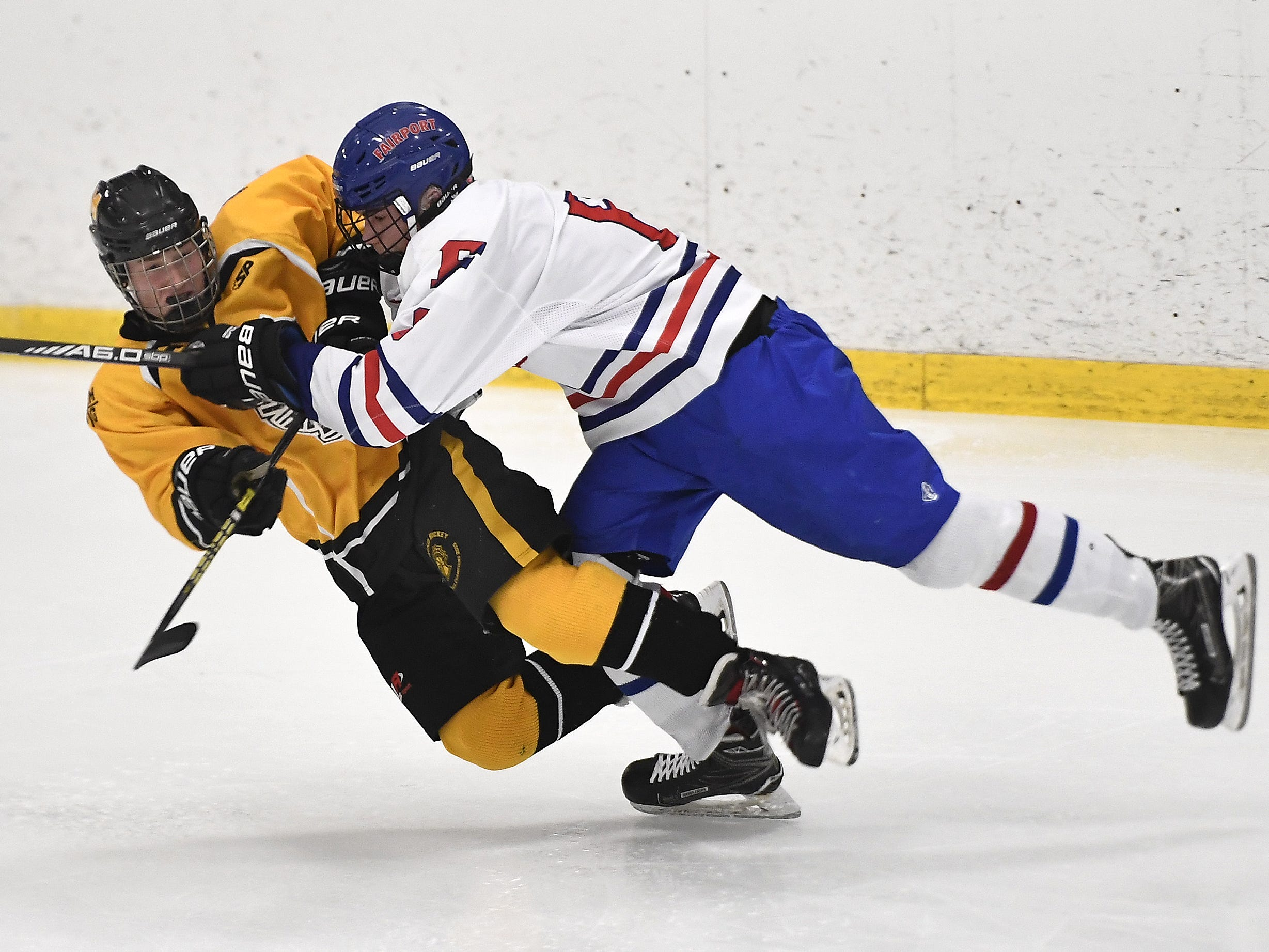 McQuaid's Sean Murray, left, gets a pass off before taking a hit from Fairport's Hunter McDonald during the second period of a regular season game played at the Rochester Ice Center, Wednesday, Feb. 6, 2019. McQuaid beat Fairport 5-4 in overtime.