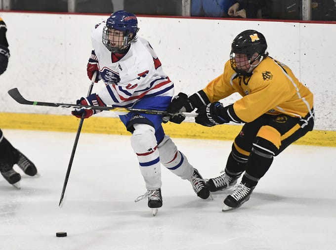 Fairport's Jake Mueller, left, is defended by McQuaid's Charlie Merkley during the second period of a regular season game played at the Rochester Ice Center, Wednesday, Feb. 6, 2019. Merkley scored the winning goal as McQuaid beat Fairport 5-4 in overtime.