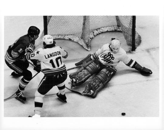 Steve Langdon helps out goalie Dave Parro against New Haven's Dale Lewis.