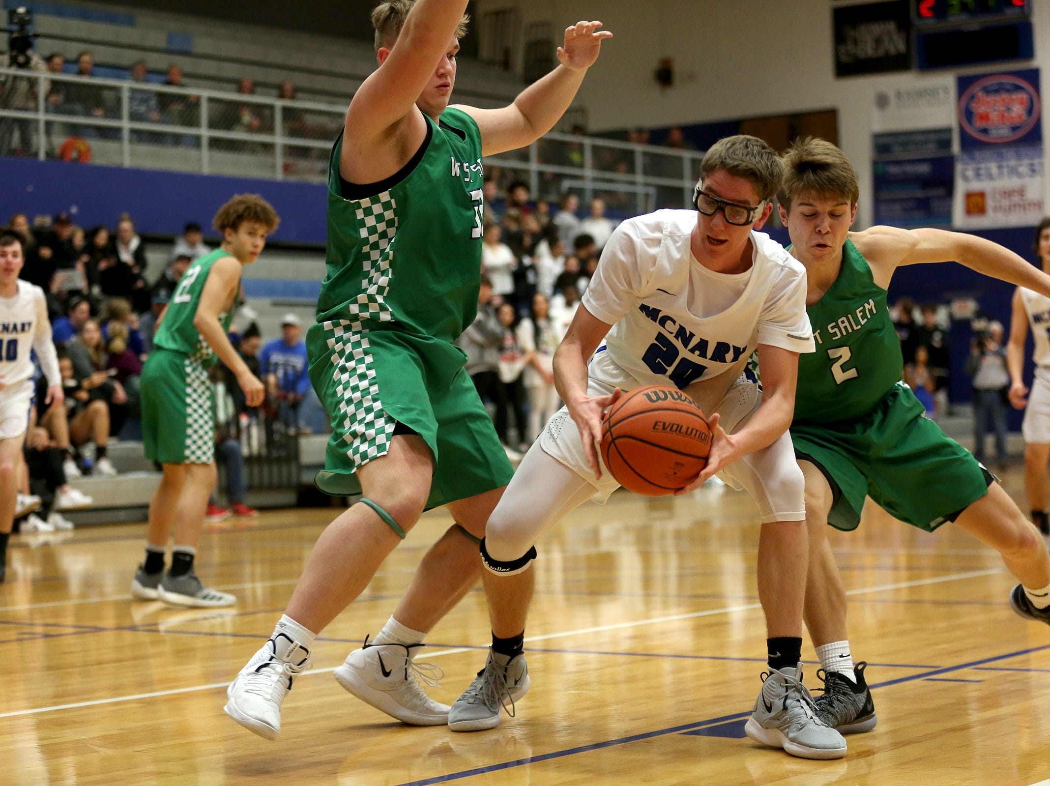 McNary's Noah Hudkins (20) protects the ball during the McNary boys basketball vs. West Salem game at McNary High School in Keizer on Wednesday, Feb. 6, 2019.