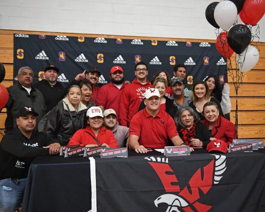 Salinas defensive lineman Sebastian Gomez (first row, red polo) became the first Cowboys football player to sign a Division I scholarship in 15 years Wednesday.
