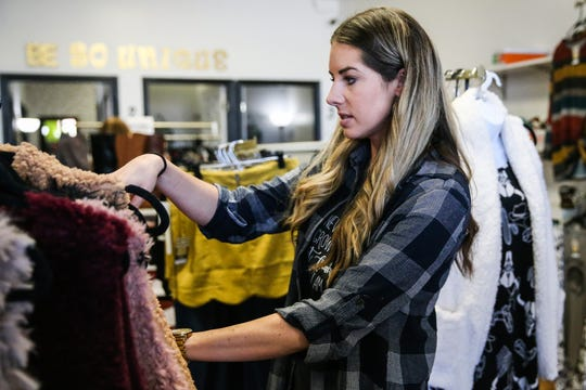 Tiffany Nelson reorganized clothes Jan. 25, 2019, at her shop So Unique Boutique.
