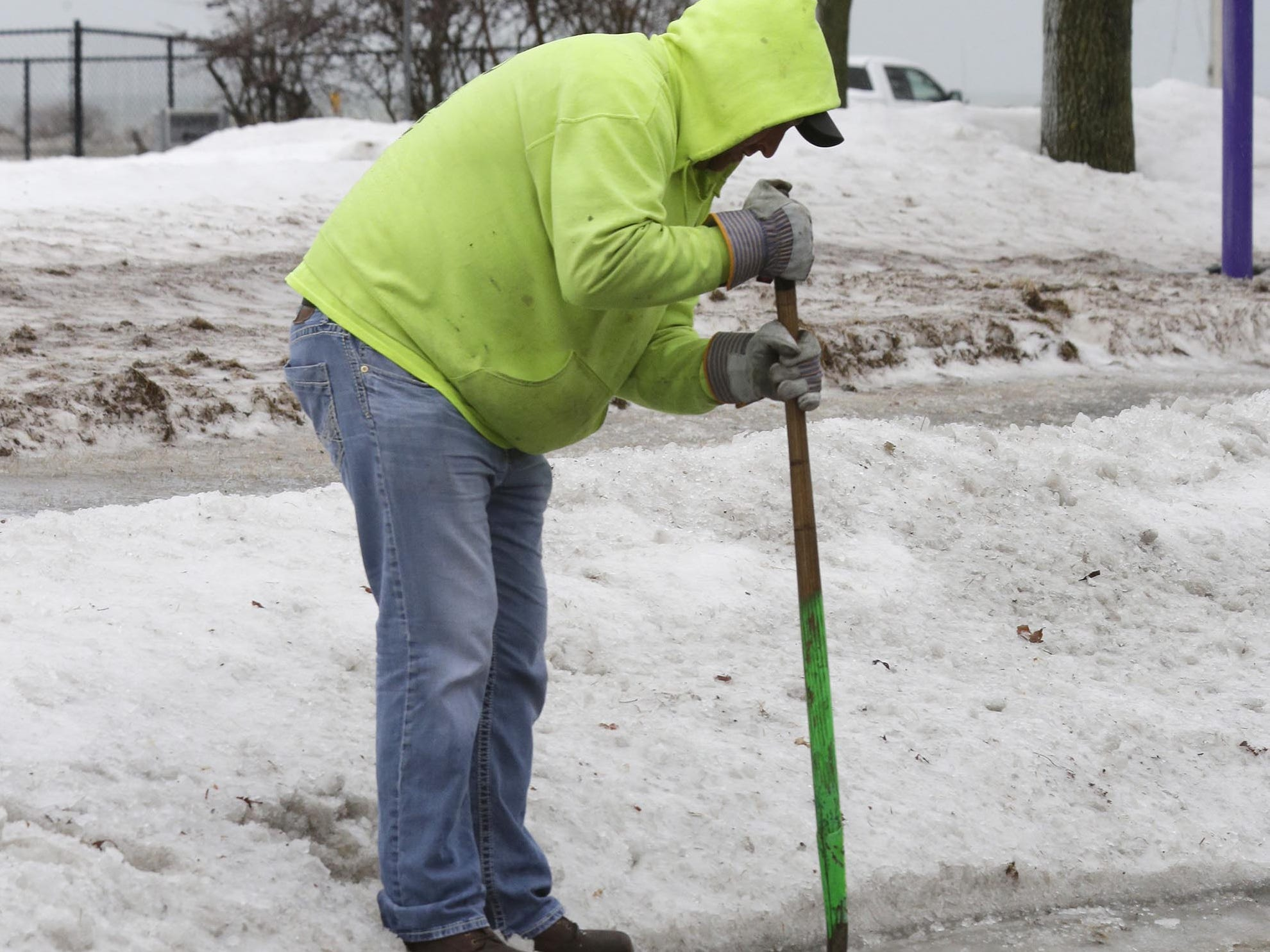 A City of Sheboygan public works employee,  who did not want to give his name, uses a shovel to unclog a drain on Broughton Drive, Tuesday, February 5, 2019, in Sheboygan, Wis. Early afternoon rain combined with frozen street drains caused localized flooding.