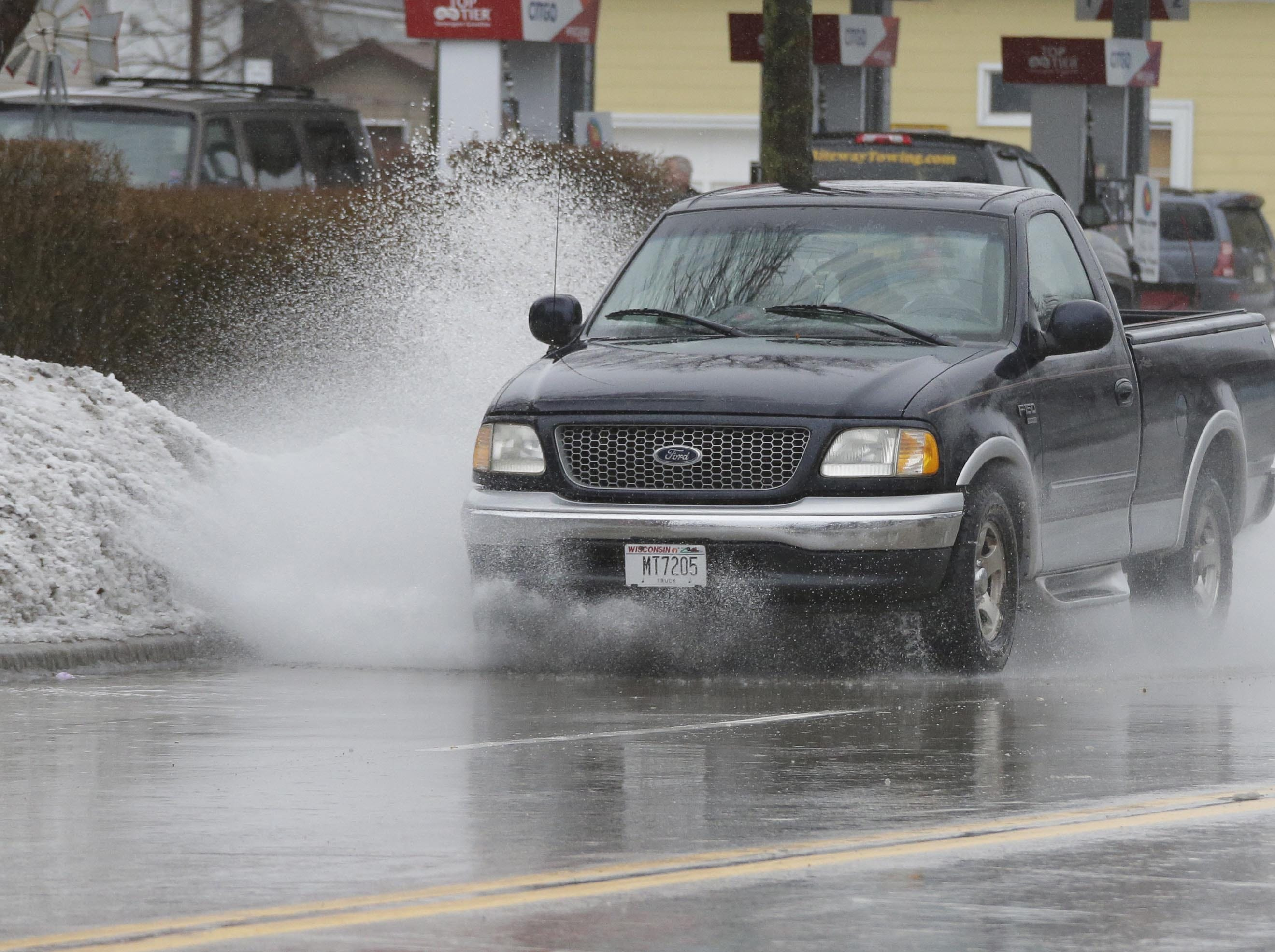 A pickup truck drives through standing water on South 14th Street, Tuesday, February 5, 2019, in Sheboygan, Wis. Early afternoon rain combined with frozen street drains caused localized flooding.