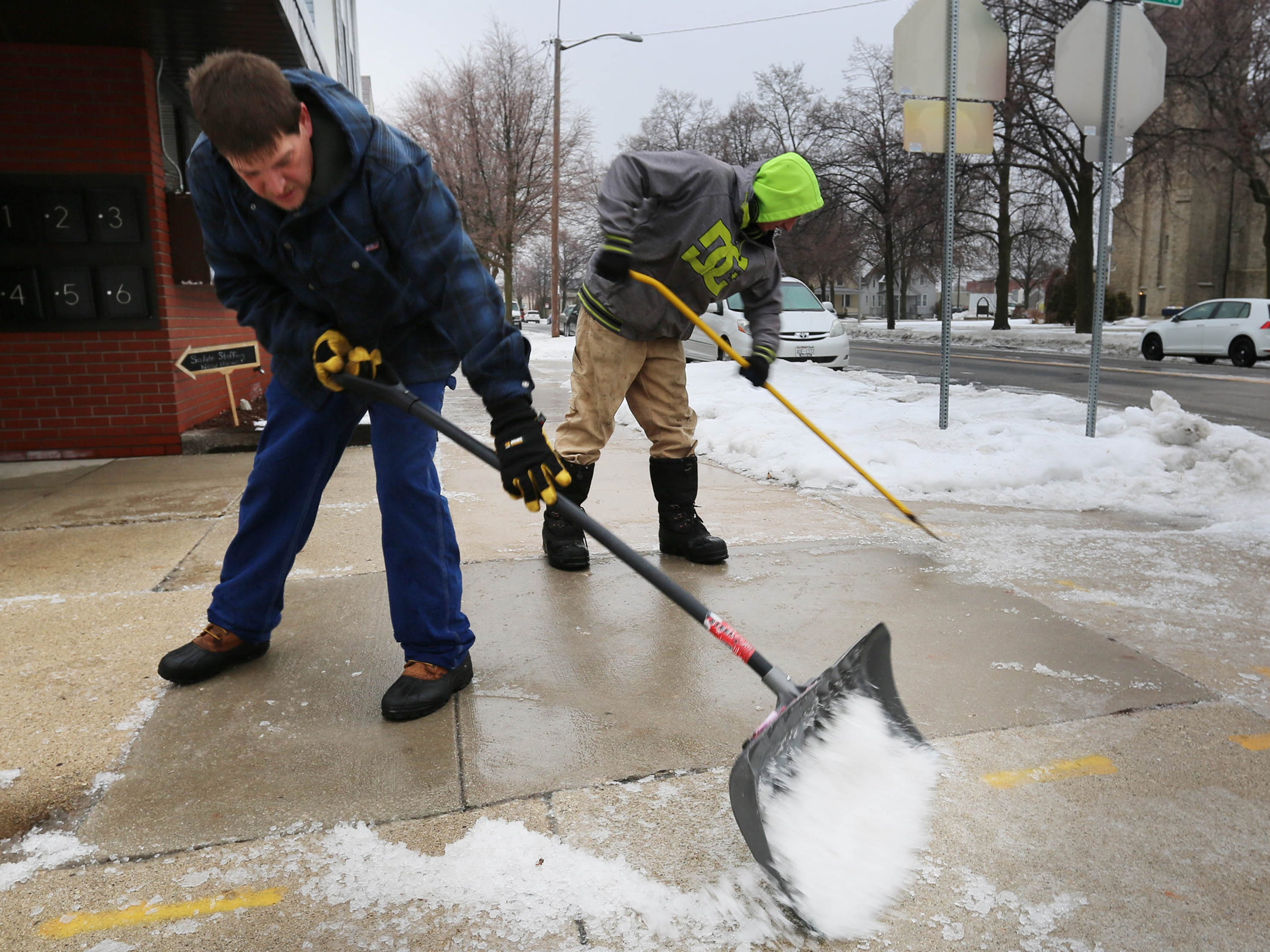 Dutcher Matyjasik, left, and Tom Wade scrape ice off sidewalk area at 8th and Superior Avenue, Tuesday, February 5, 2019, in Sheboygan, Wis. 