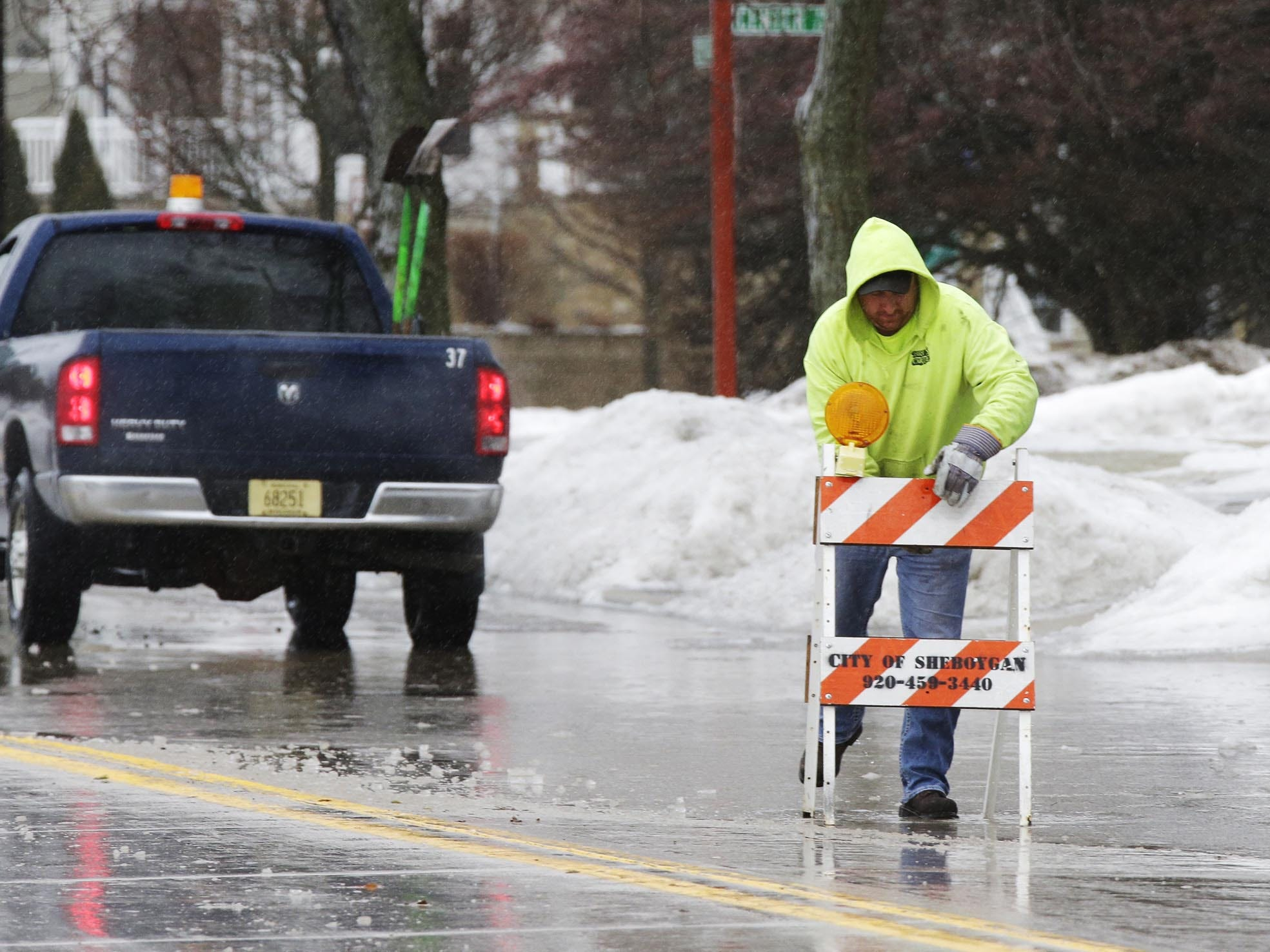 A City of Sheboygan public works employee, who did not want to give his name, places a caution sign by a water clogged Broughton Drive, Tuesday, February 5, 2019, in Sheboygan, Wis. Early afternoon rain combined with frozen street drains caused localized flooding.