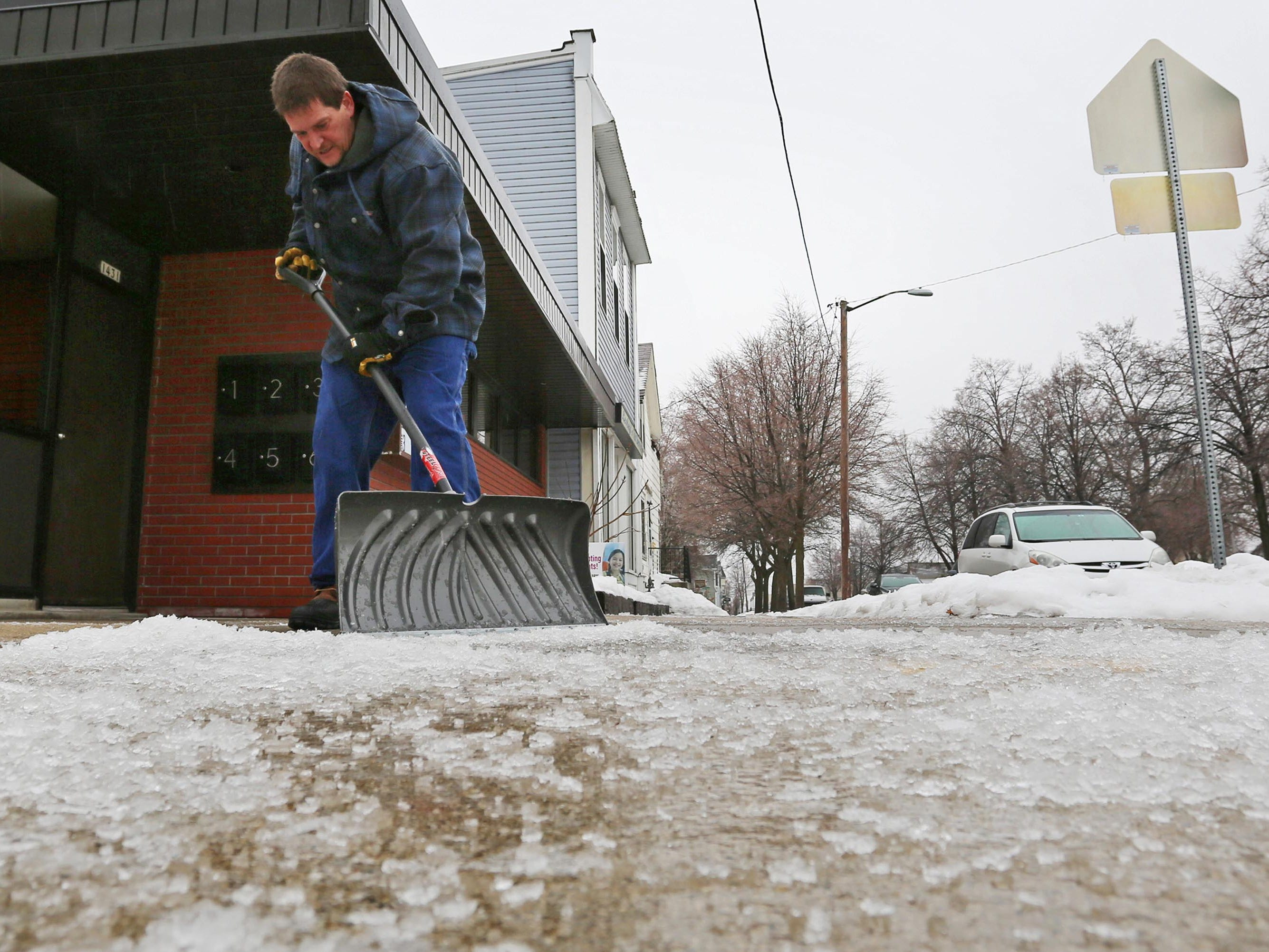 Dutcher Matyjasik scrapes off ice sidewalk at 8th and Superior Avenue, Tuesday, February 5, 2019, in Sheboygan, Wis. 