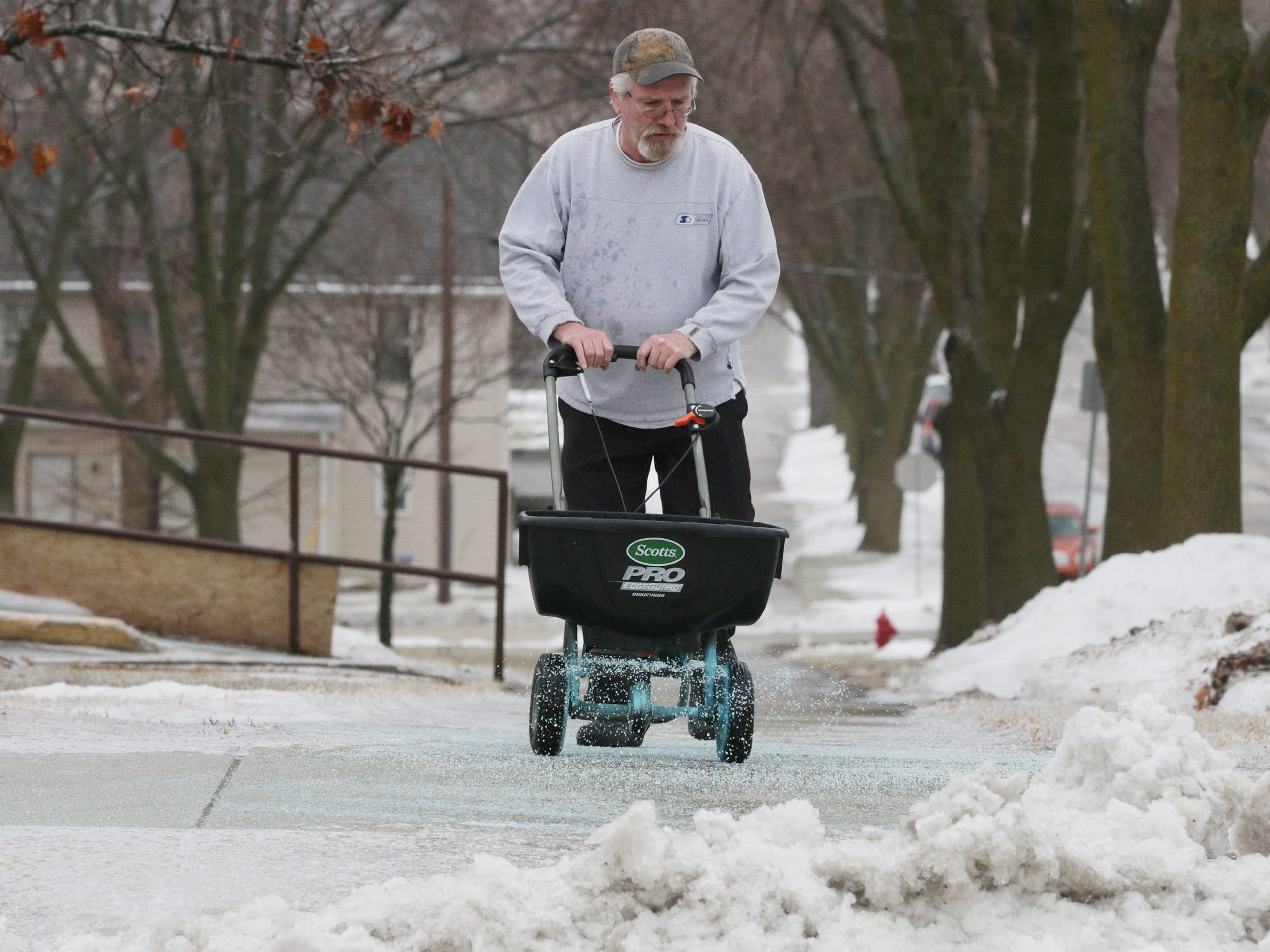 "Chuck McDonell, who maintains sidewalks at Park Plaza housing on North 9th Street, spreads salt, Tuesday, February 5, 2019, in Sheboygan, Wis. McDonell said, ""This is already my fourth time salting today.""