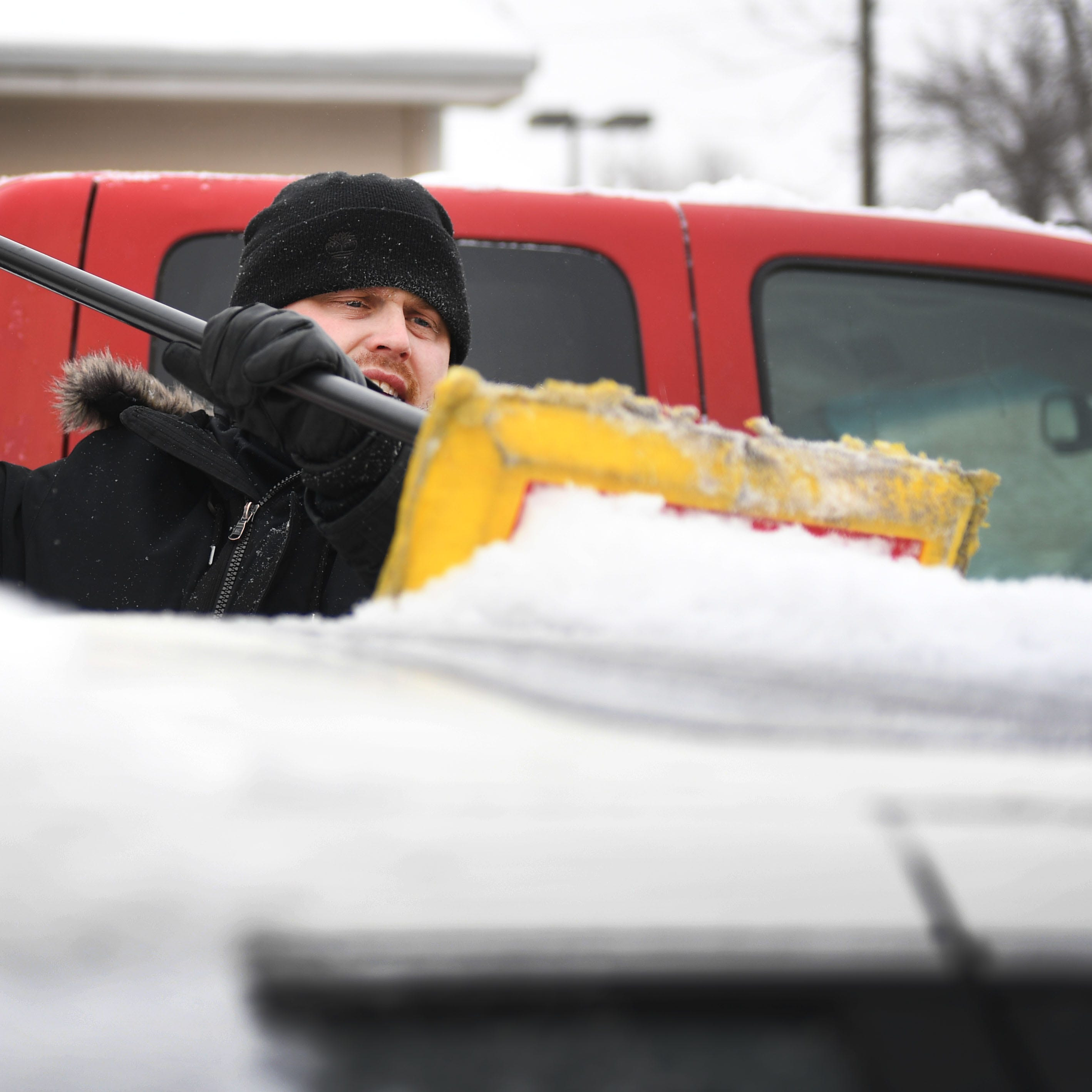 Jonathan Leise, management at Imperial Group, cleans the cars in the dealership's lot Thursday, Feb. 7, in Sioux Falls. Sioux Falls is under a blizzard warning until midnight.
