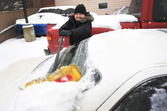Jonathan Leise, management at Imperial Group, cleans the cars in the dealership's lot Thursday, Feb. 7, in Sioux Falls. Leise said it usually takes about two days to clean the cars, top them with gas, run them and check their batteries after it snows. Sioux Falls is under a blizzard warning until midnight.