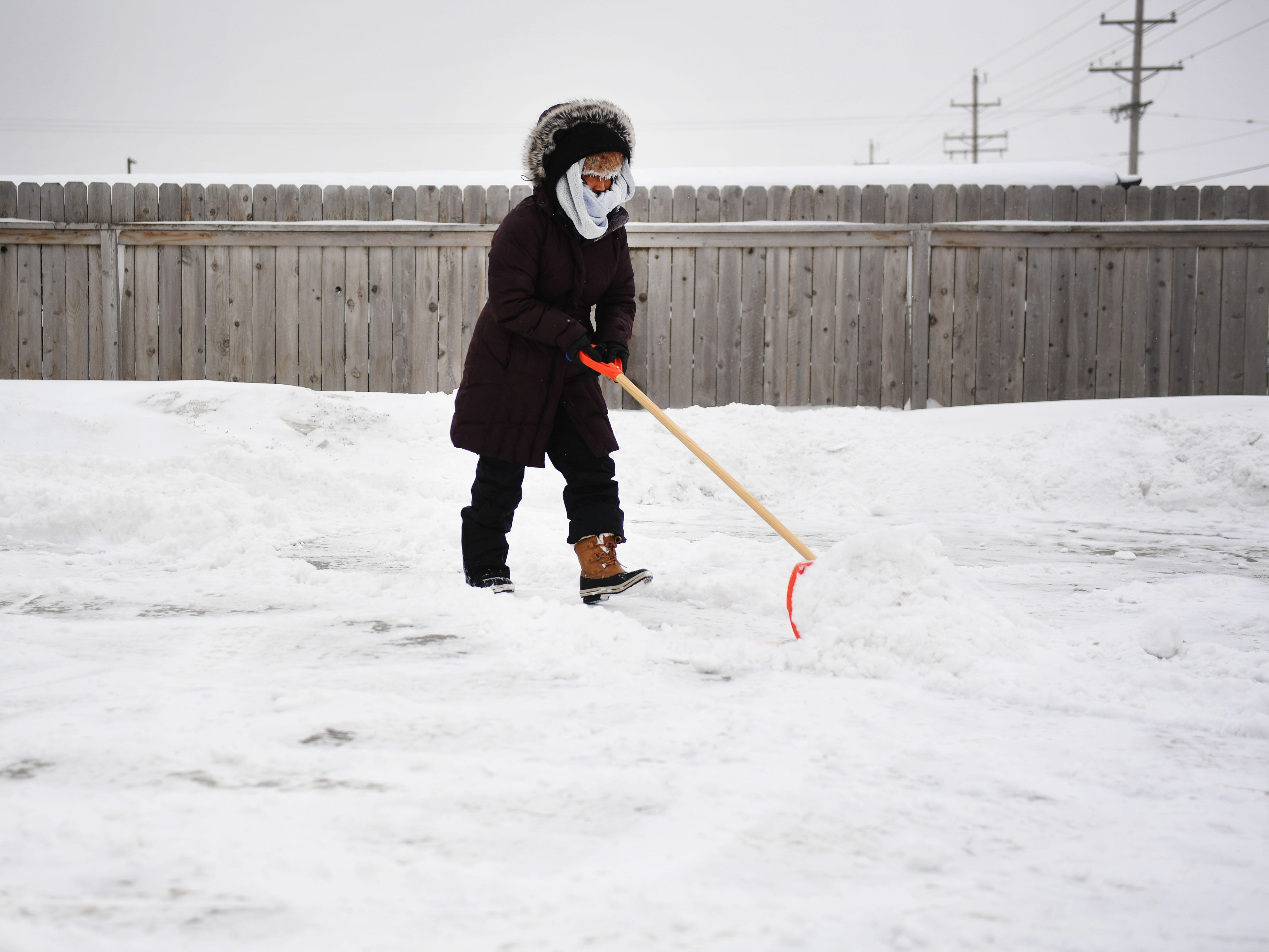 Sonia Zetino shovel her driveway Thursday, Feb. 7, in Sioux Falls. Sioux Falls is under a blizzard warning until midnight.
