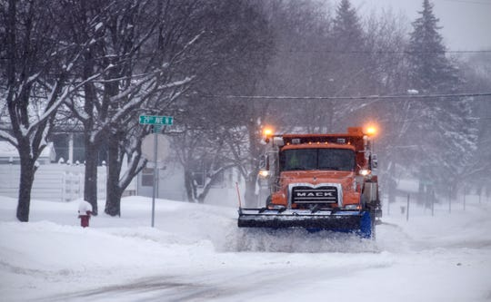 A St. Cloud plow clears a stretch of Seventh Avenue North as snow continues to fall Thursday, Feb. 7, in St. Cloud.