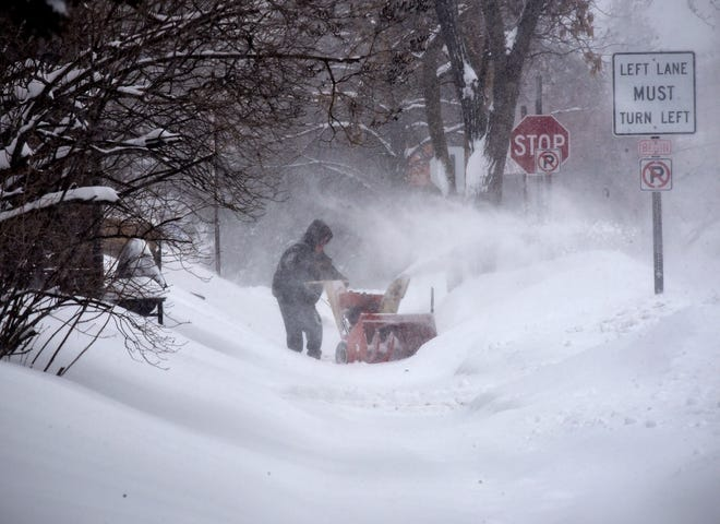 A resident clears a driveway as heavy snow continues to fall Thursday, Feb. 7, in St. Cloud. A snow emergency was declared for Friday in St. Cloud due to high winds and possible continued snowfall.