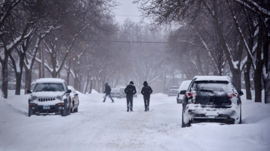 People walk down a snow-covered section of 18th Avenue North Thursday afternoon in St. Cloud.