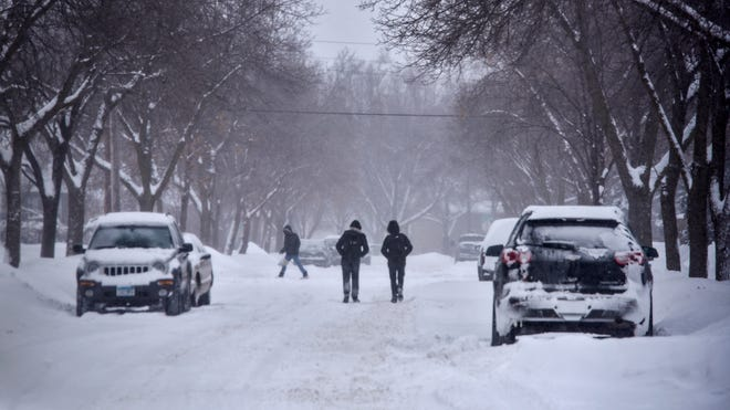 People walk down a snow-covered section of 18th Avenue North Thursday, Feb. 7 in St. Cloud.
