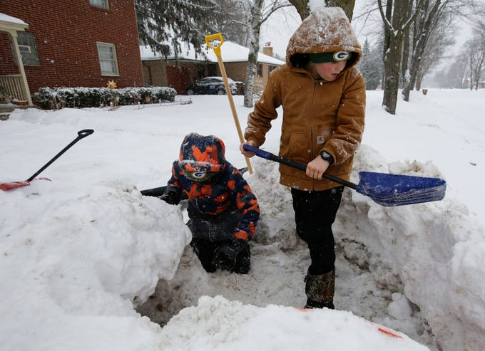Sebastian Cole, left, 11, and Brock Huebner, 11, build a snow fort on Thursday, February 7, 2019, in Stevens Point, Wis. A winter storm is expected to drop 5-8 inches of snow in the area by the time it clears Thursday evening.